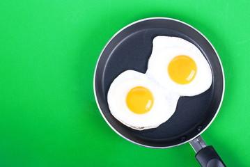 Fond de hotte en verre imprimé Ouf fried eggs in a pan two eggs on a green background