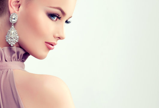 Beautiful girl with evening makeup and  large earrings jewelry .