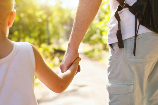 child holding hand of adult parent outside in summer park