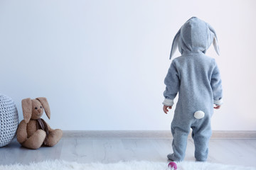 Cute little child in bunny costume standing at home Fototapete