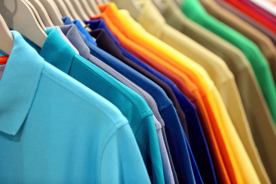 Row of men's polo shirts in wardrobe or store