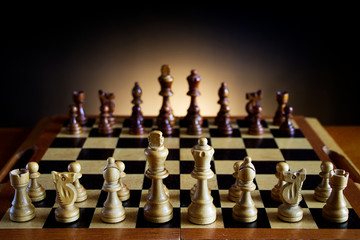 ready for a game of chess, wooden chessboard on a table, dark gradient background
