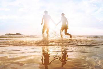 happy young couple having fun on the beach at sunset, water splash, enjoying life