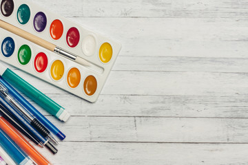 Watercolors and markers with handles on a wooden table