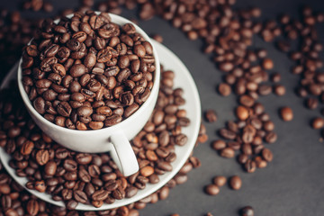 Coffee beans in a cup and in a white saucer