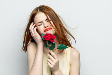 upset woman crying on a gray background, red flower
