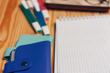 colorful markers notebook and business card on a wooden table