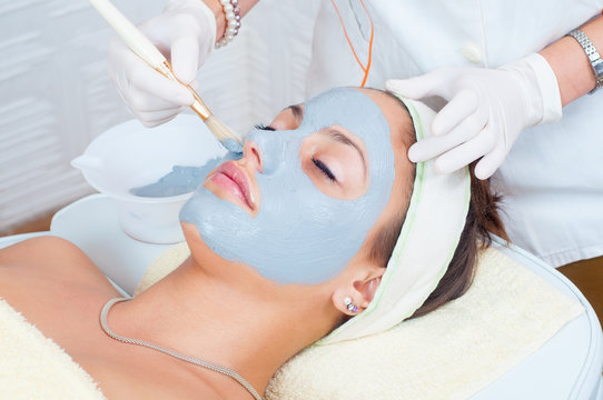 Woman lying on massage table in health spa while facial mask is applied on her face