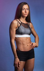 athletic muscular fit woman isolated on studio blue background