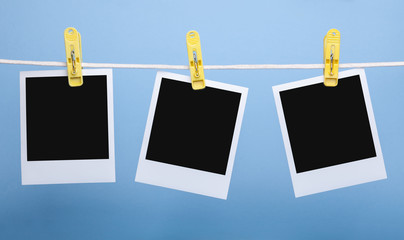 three blank insta photo frames on clothes pins on rope isolated on blue background