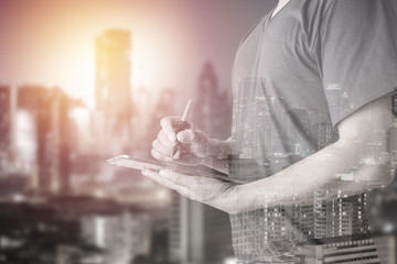 Double exposure of businessman using digital tablet with city landscape blurred background
