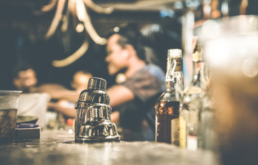 Blurred defocused side view of barman and people drinking and having fun at cocktail bar - Social gathering concept with people enjoying time together - Warm retro contrast filter with focus on shaker