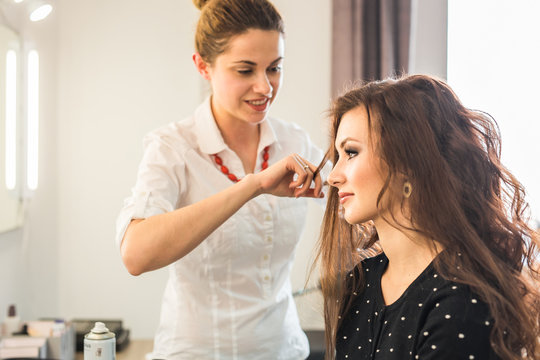 Beautiful woman getting haircut by hairdresser in the beauty salon.