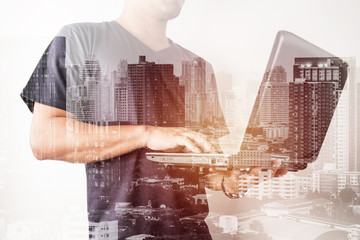 Double exposure of success businessman using labtop with with city landscape background