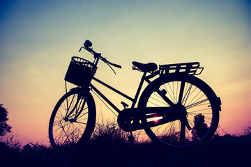 beautiful landscape image with silhouette Bicycle at sunset