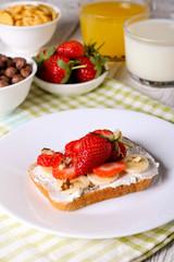 breakfast: Fresh toast with strawberry, banana and nuts, cornflakes, orange juice, milk