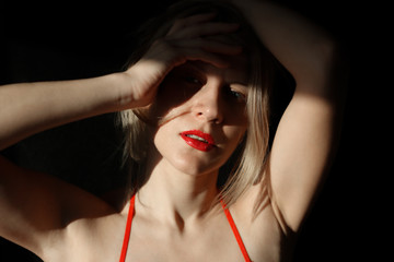 pensive blonde woman close-up with red lips