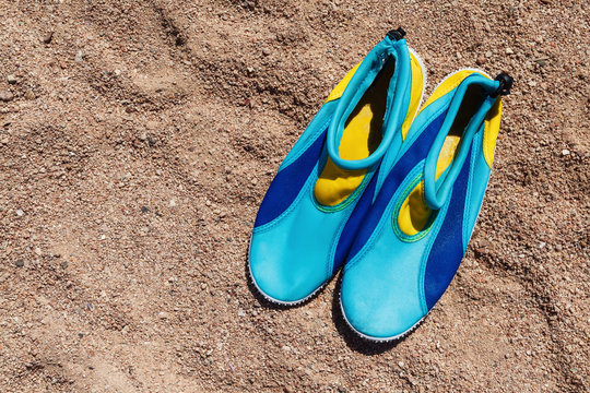 yellow-blue shoes that protect feet from the coral on the beach
