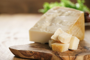 hard parmesan cheese cubes on olive cutting board, closeup photo