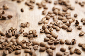 roasted coffee beans falling on wood table, shallow focus