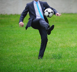 Businessman in suit plays football on a nature background.