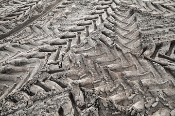 Tractor tire tracks on wet gray ground