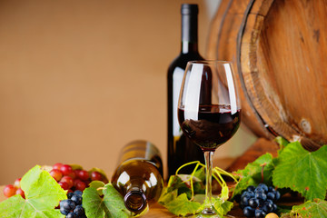 Wine bottles, glass, grapes and barrel