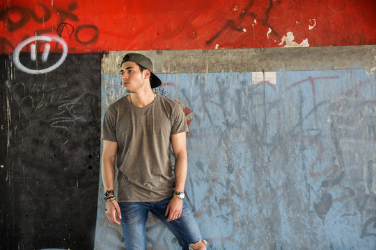 Attractive young man standing against colorful wall, looking away