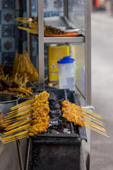 Chicken satay sticks being cooked over charcole at asian street food vendor.