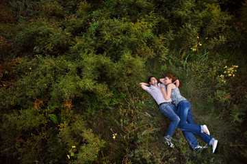 Couple lying down on the grass. Man admiring the sky and the girl looking at him lovingly