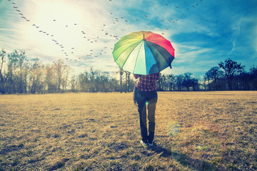 woman holding rainbow umbrella and watching sunset in the nature, birds flying above ,spring background