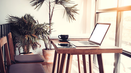 Office workplace with laptop on wood table against the windows.