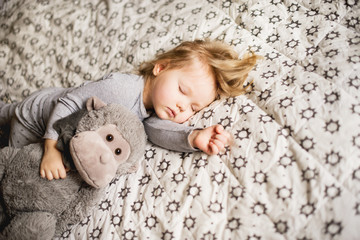 Little girl sleeping with a toy on the bed