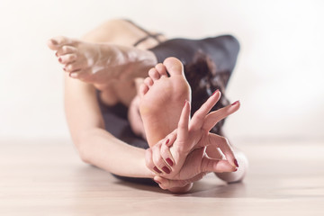 Woman doing yoga meditation and stretching exercises bending forward with her leg behind head.
