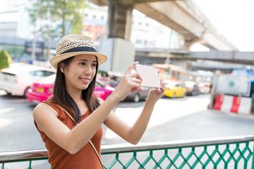Woman taking photo on mobile phone in Bangkok