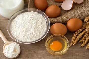 Eggs, flour and milk on wooden background.