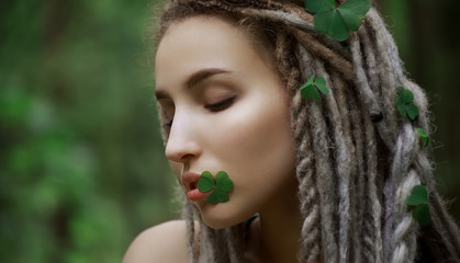 Very beautiful girl with a clover in her lips and hair. Beauty and nature concept