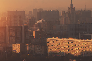 Close-up shooting from top of metropolitan city: residential buildings and districts illuminated by morning sun, towers, smoke and chimneys, multiple facades, windows, hazy horizon, Moscow, Russia