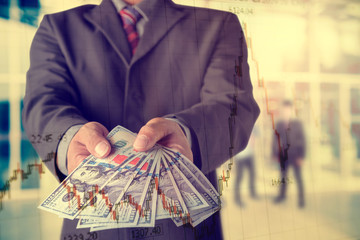 Businessman with money in hand, US dollar (USD) bills - investment, success and profitable business concepts.with stock chart, investment concept.