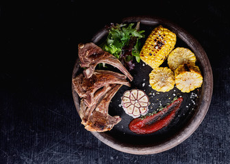 Grilled lamb ribs served with grilled corn, salat, bbq sauce, garlic, salt pepper on a rustic ceramic plate. Top View