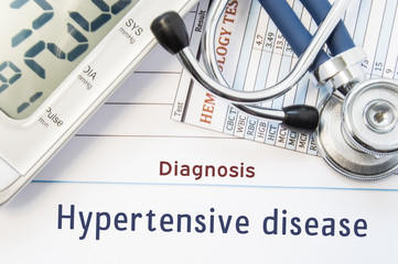 Diagnosis Hypertensive disease. Stethoscope, hematology blood test result and digital tonometer lie on sheet of paper with printed title diagnosis of vascular disease Hypertensive disease