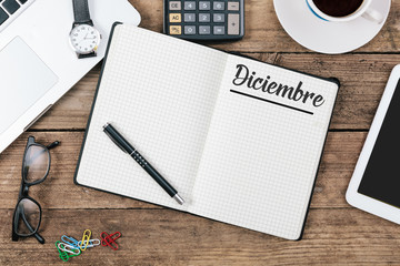 Diciembre (Spanish December) month name on paper note pad at office desk