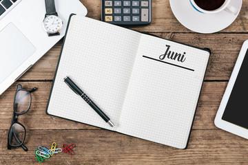 Juni (German June) month name on paper note pad at office desk