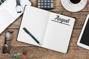 August (German and English) month name on paper note pad at office desk