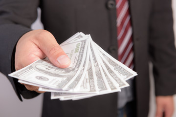 Businessman with money in hand, US dollar (USD) bills.