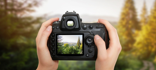 Women holding camera in hands and taking photo of nature