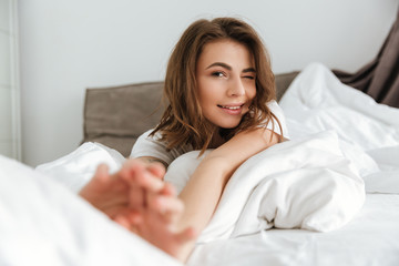 Attractive relaxed young woman lying and stretching in bed