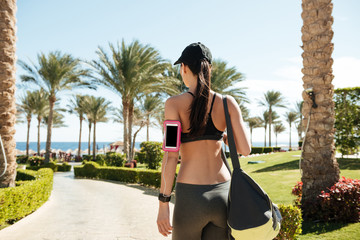 Fitness woman with bag and blank screen cell phone