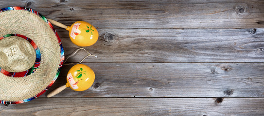 Traditional maracas and large sombrero for Cinco de Mayo holiday party celebration on rustic wooden boards