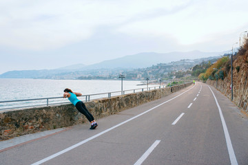 Young woman in sport on the sea coast